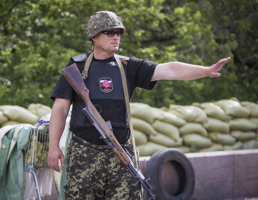 An armed member of the separatist group called the Russian Orthodox Army stops a car at a checkpoint in the Ukraine city of Donetsk this week.