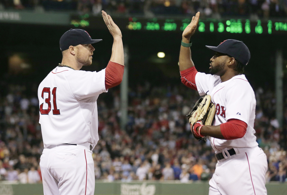 Boston Red Sox starting pitcher Jon Lester, left, congratulates center fielder Jackie Bradley Jr. after catching a fly out by Cleveland Indians Michael Bourn, and throwing out base runner Mike Aviles off first, to end the top of the seventh inning on Thursday.