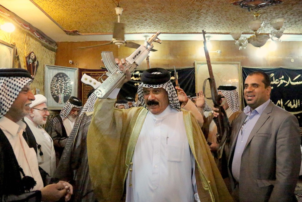 Iraqi Shiite tribal leaders chant slogans against the al-Qaida-inspired Islamic State of Iraq and the Levant (ISIL), in Baghdad on Friday. The leaders met in Sadr City and declared their readiness to take up arms against the al-Qaida inspired group.