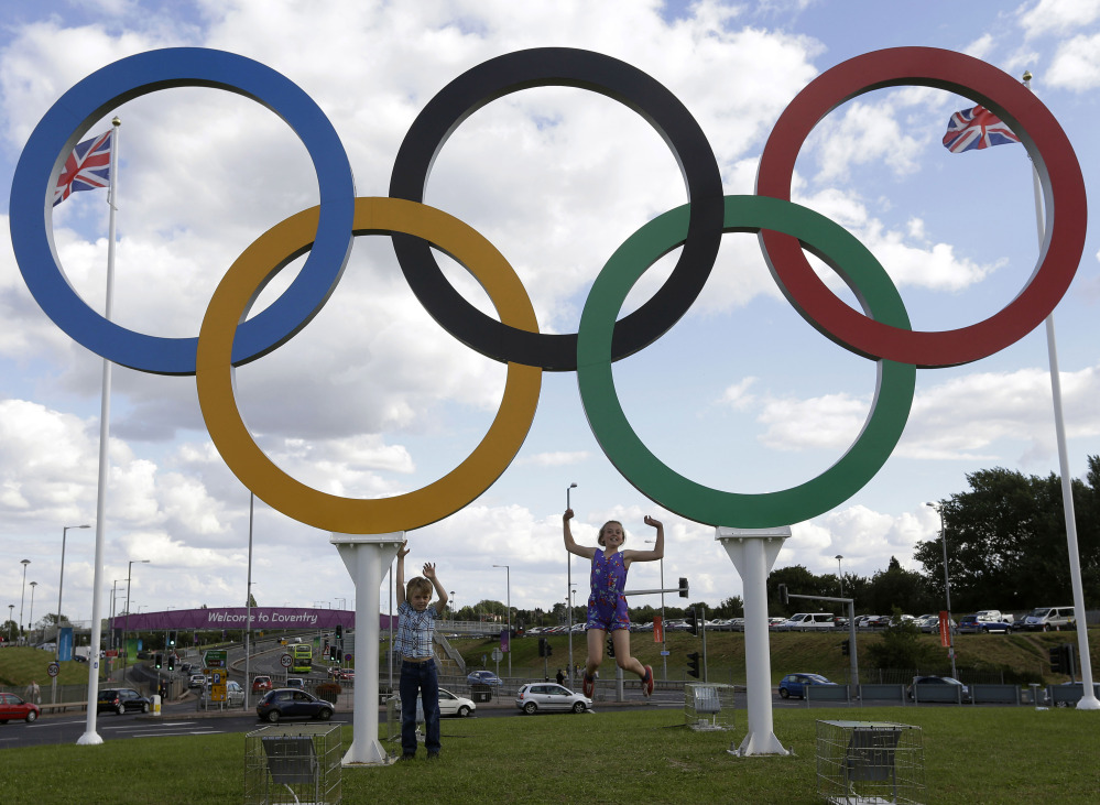 In this July 28, 2012 file photo, British children pose for photos under a sculpture of the Olympics rings, in Coventry, England. Boston, Los Angeles, San Francisco and Washington are the cities still in the running for a possible U.S. bid to host the 2024 Summer Olympics.