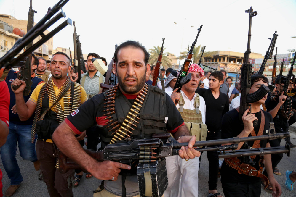Iraqi Shiite tribal fighters deploy with their weapons while chanting slogans against the al-Qaida-inspired Islamic State of Iraq and the Levant, in order to help the military in defending the capital in Baghdad's Sadr City, Iraq, on Friday.