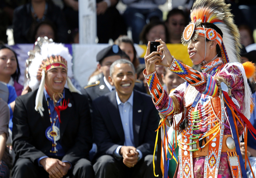 A dancer takes a selfie with President Obama, and chairman if the Standing Rock Sioux Tribe David Archambault, left, at Standing Rock Indian Reservation in Cannon Ball, N.D., on Friday