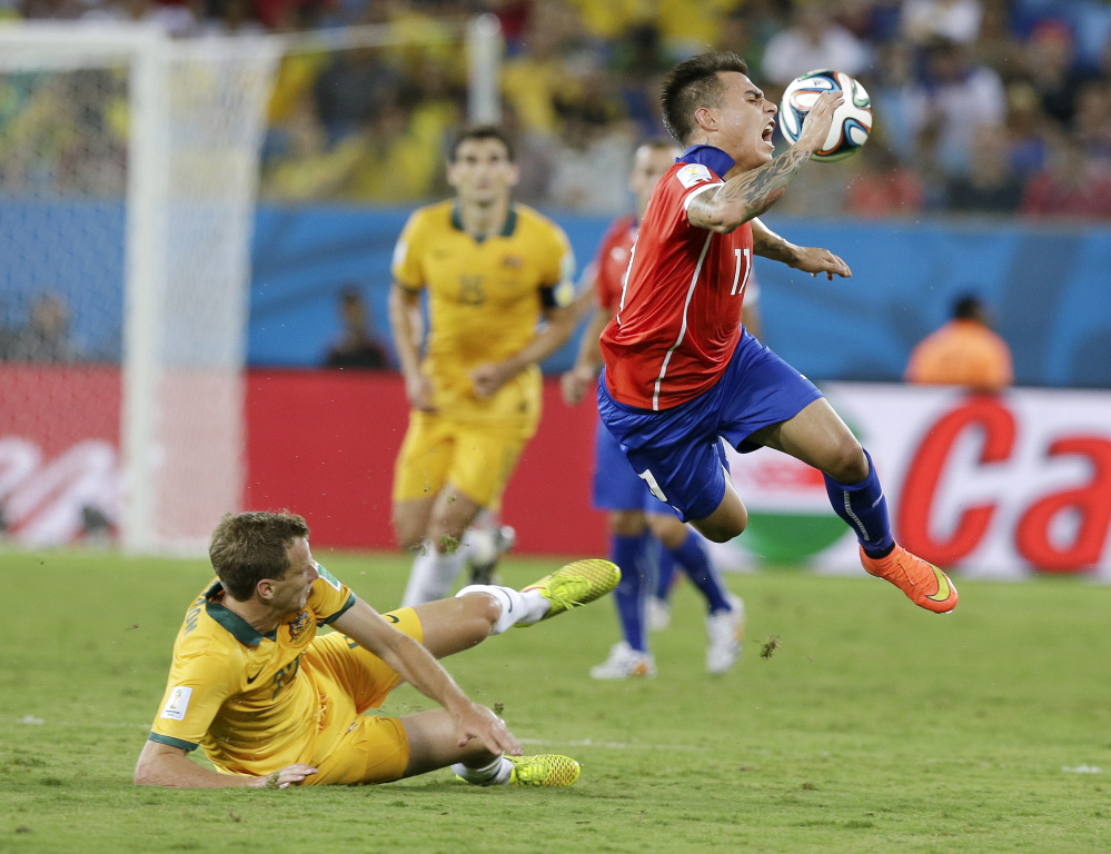 Australia's Alex Wilkinson, left, trips up Chile's Eduardo Vargas (11) during the first half of the group B World Cup soccer match between Chile and Australia in the Arena Pantanal in Cuiaba, Brazil, Friday, June 13, 2014.