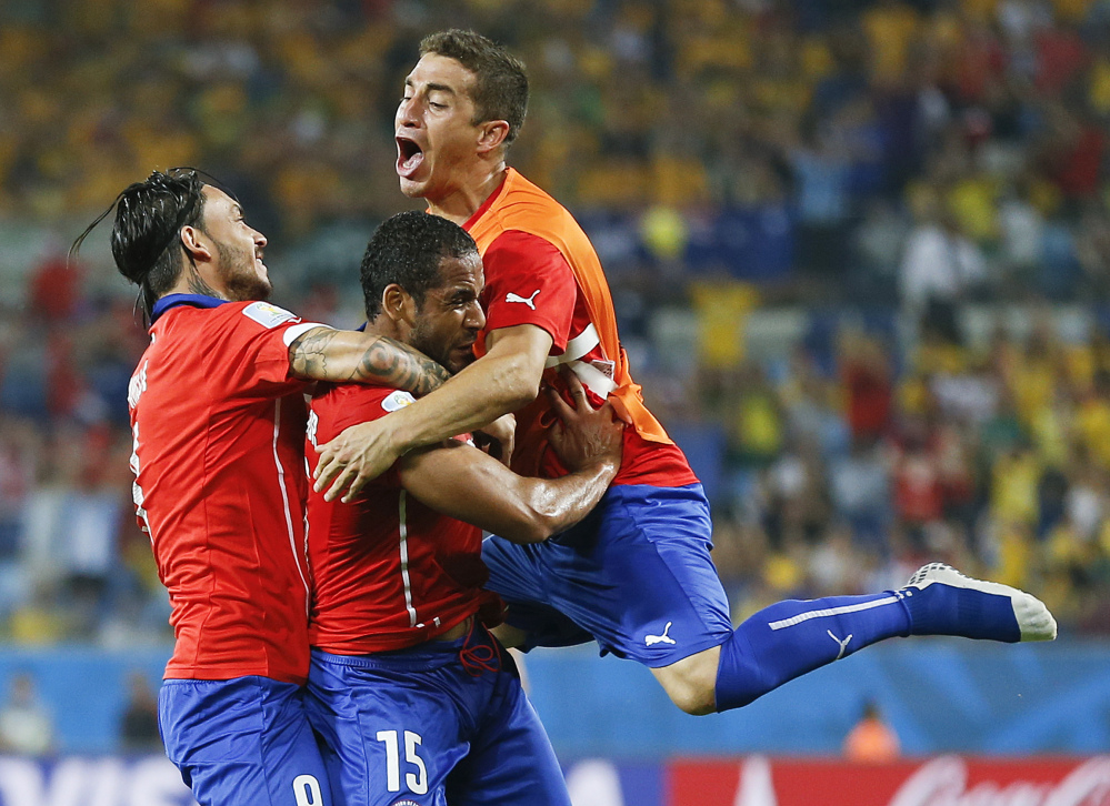 Chile's Jean Beausejour, center, celebrates with teammates after scoring his side's third goal during the group B World Cup soccer match between Chile and Australia in the Arena Pantanal in Cuiaba, Brazil, Friday, June 13, 2014.