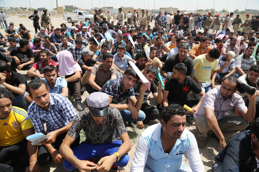 Iraqi men gather outside of the main army recruiting center to volunteer for military service in Baghdad, Iraq on Saturday after authorities urged Iraqis to help battle insurgents.