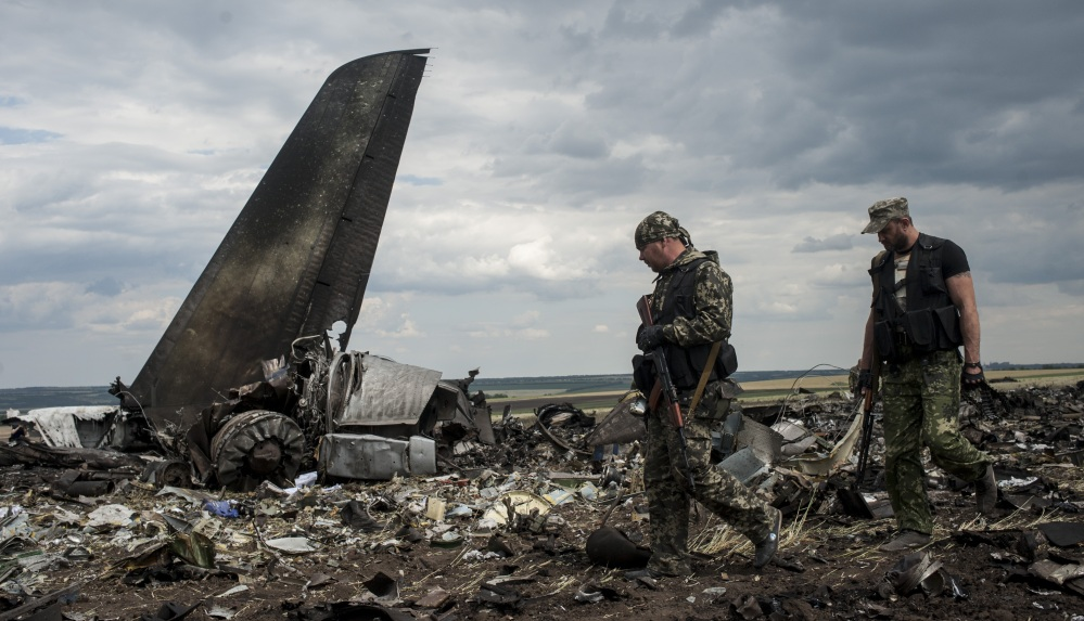 Pro-Russian fighters walk past the remains of a downed Ukrainian military transport plane at the airport near Luhansk, Ukraine, on Saturday. All 49 aboard were killed.
