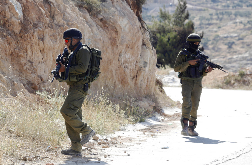 Israeli soldiers patrol during a military operation to search for three missing teenagers near the West Bank city of Hebron on Saturday. Israel's president lays blame for the abduction on the Palestinian Authority. Among the three who are missing is an American. The teens were reportedly hitchhiking when they were kidnapped.