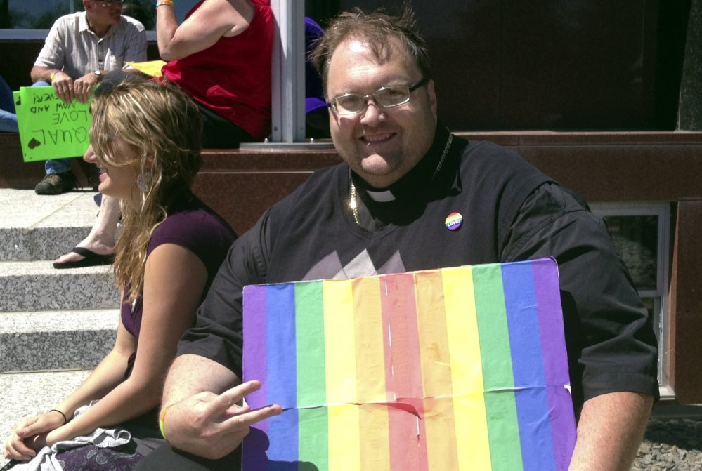 The Rev. Scott Crandall of Peace United Church of Christ joins 1demonstrators in front of the Portage County Courthouse on Friday in Stevens Point, Wis. About 50 people gathered to protest the county's refusal to issue same-sex marriage licenses.
