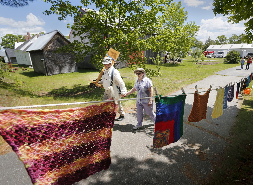 A couple leave the Maine Fiber Frolic at the Windsor Fairgrounds. Derek Davis/Staff Photographer