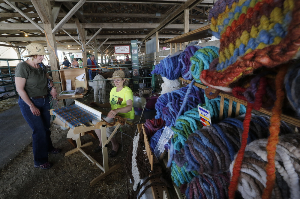 Jane Berlew of Falmouth watches as Pam Harwood of Longwoods Alpaca Farm weaves a rug at the Maine Fiber Frolic. Derek Davis/Staff Photographer