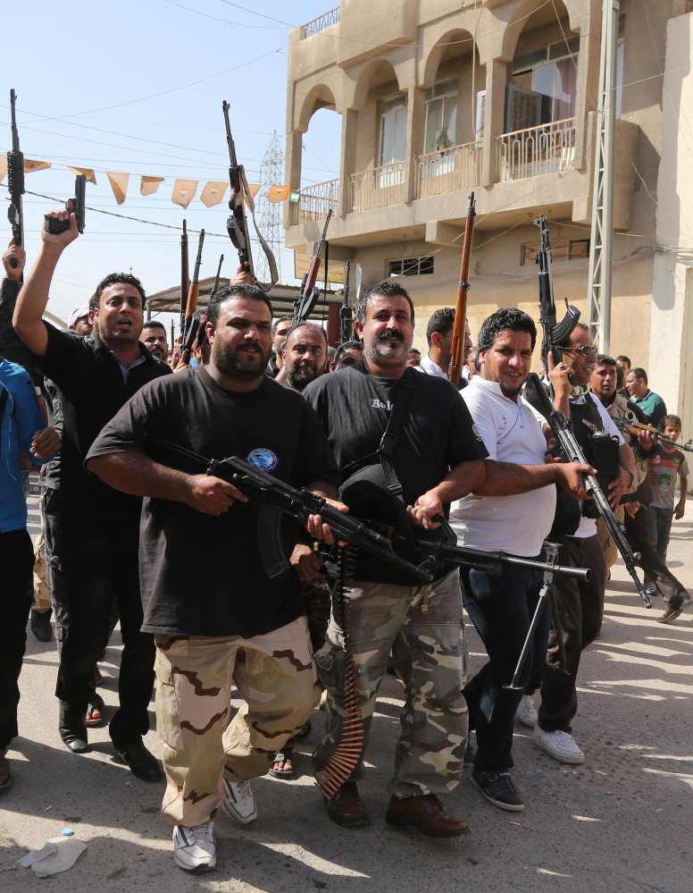 Shiite tribal fighters raise their weapons and chant slogans against the al-Qaida-inspired Islamic State of Iraq and Syria in Baghdad's Sadr City on Saturday.