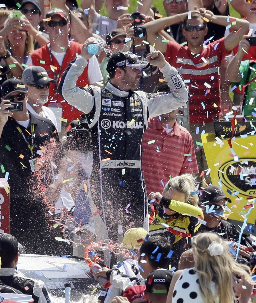 Jimmie Johnson celebrates in Victory Lane after the NASCAR Quicken Loans 400 auto race at Michigan International Speedway in Brooklyn, Mich., Sunday.