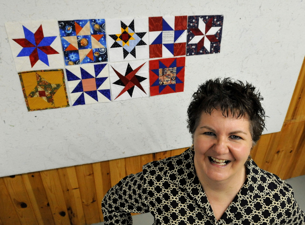Nadine Villani, a member of the Somerset Samplers, stands next to several quilted squares with space themes at Pinwheels Quilting on West Front Street in Skowhegan.