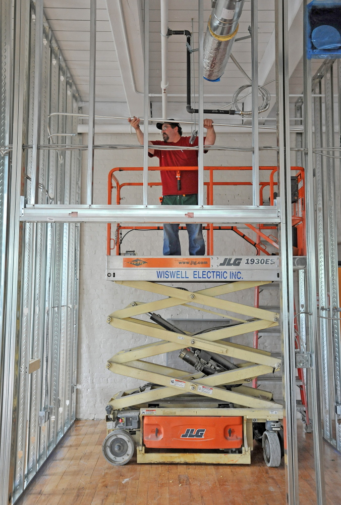 Contractor Jon Madore installs electrical conduit in a section of the new MaineGeneral medical offices in the Hathaway Center on Water Street in Waterville on Thursday.