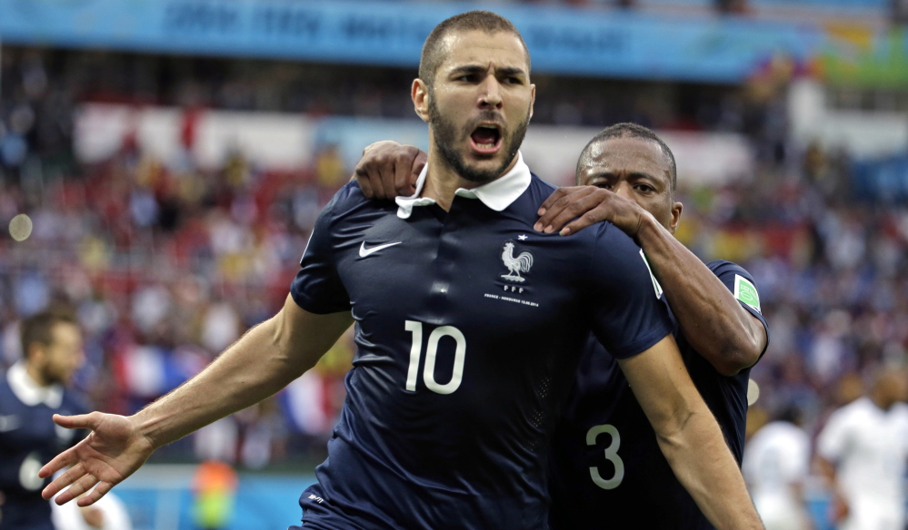 France's Karim Benzema celebrates with teammate Patrice Evra after scoring the first of his two goals on a penalty kick during the Group E World Cup match between France and Honduras on Sunday at the Estadio Beira-Rio in Porto Alegre, Brazil. France never allowed a shot at its own net and won 3-0.
