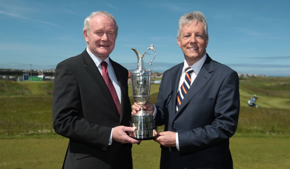 Northern Ireland Deputy First Minister Martin McGuinness, left, and First Minister Peter Robinson hold the Claret Jug trophy for the media to announce that golf's oldest championship would return to Royal Portrush in Northern Ireland, Monday.