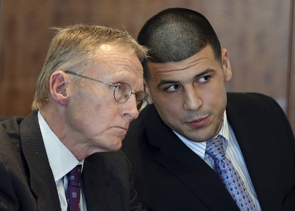 In this Friday, Feb. 7, 2014, file photo, former New England Patriots football player Aaron Hernandez, right, speaks to his attorney Charles Rankin during a hearing at Bristol Superior Court, in Fall River, Mass.
