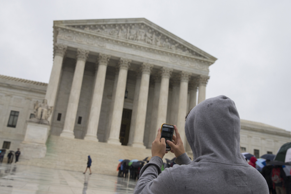 """A visitor to the Supreme Court uses his cellphone to take a photo of the court in Washington. A divided Supreme Court sided with gun control groups and the Obama administration Monday, upholding a federal ban on """"straw"""" purchases of guns."""