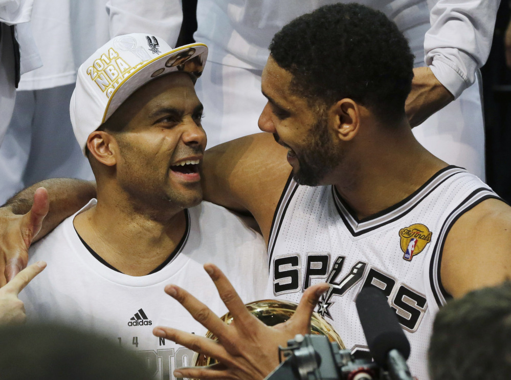 San Antonio Spurs guard Tony Parker, left, and forward Tim Duncan celebrate after Game 5 of the NBA basketball finals on Sunday, June 15, 2014, in San Antonio. The Spurs won the NBA championship 104-87.