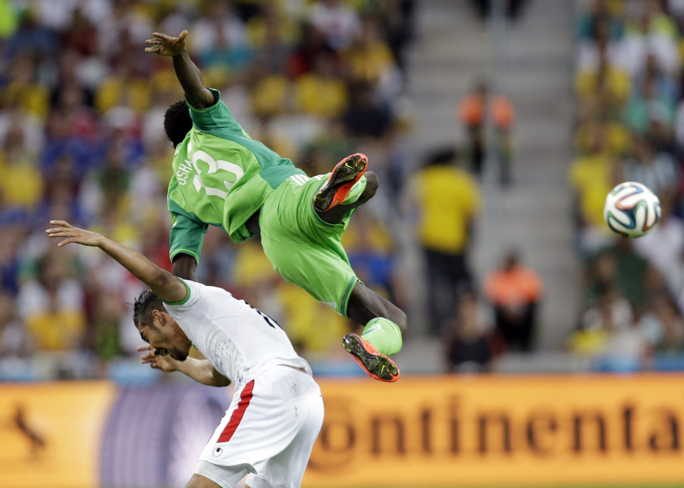 Nigeria's Juwon Oshaniwa, top, and Iran's Reza Ghoochannejhad battle for the ball during the group F World Cup soccer match between Iran and Nigeria at the Arena da Baixada in Curitiba, Brazil, Monday, June 16, 2014.