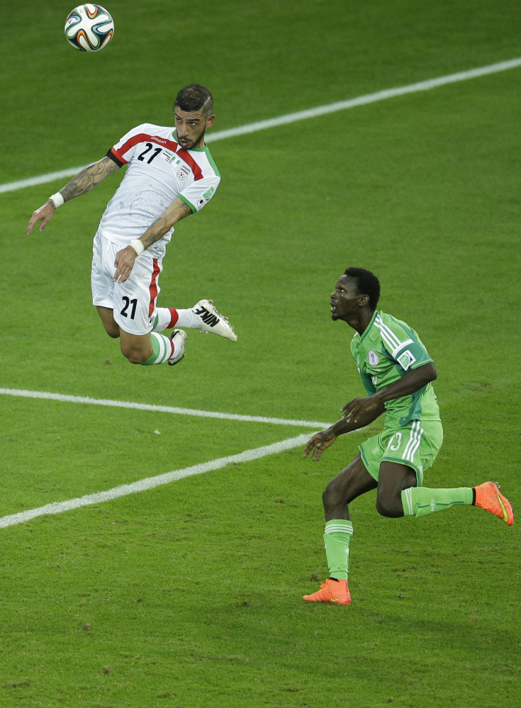 Iran's Ashkan Dejagah heads a ball as Nigeria's Juwon Oshaniwa, right, looks on during the group F World Cup soccer match between Iran and Nigeria at the Arena da Baixada in Curitiba, Brazil, Monday, June 16, 2014. The match ended in a goalless draw.