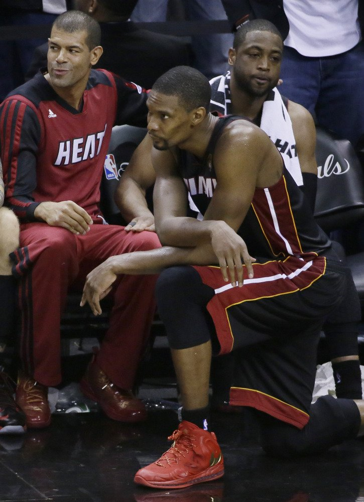 From left, Miami Heat forward Shane Battier,  center Chris Bosh and guard Dwyane Wade watch the final moments of Game 5 in the NBA basketball finals on Sunday, June 15, 2014, in San Antonio. San Antonio won the NBA championship 104-87.