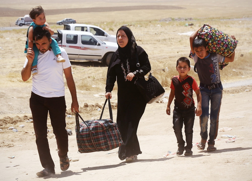 Residents of Mosul, who fled the largest city in northern Iraq because of violence by Islamic insurgents who seized the city, arrive Monday at a refugee camp outside Irbil.