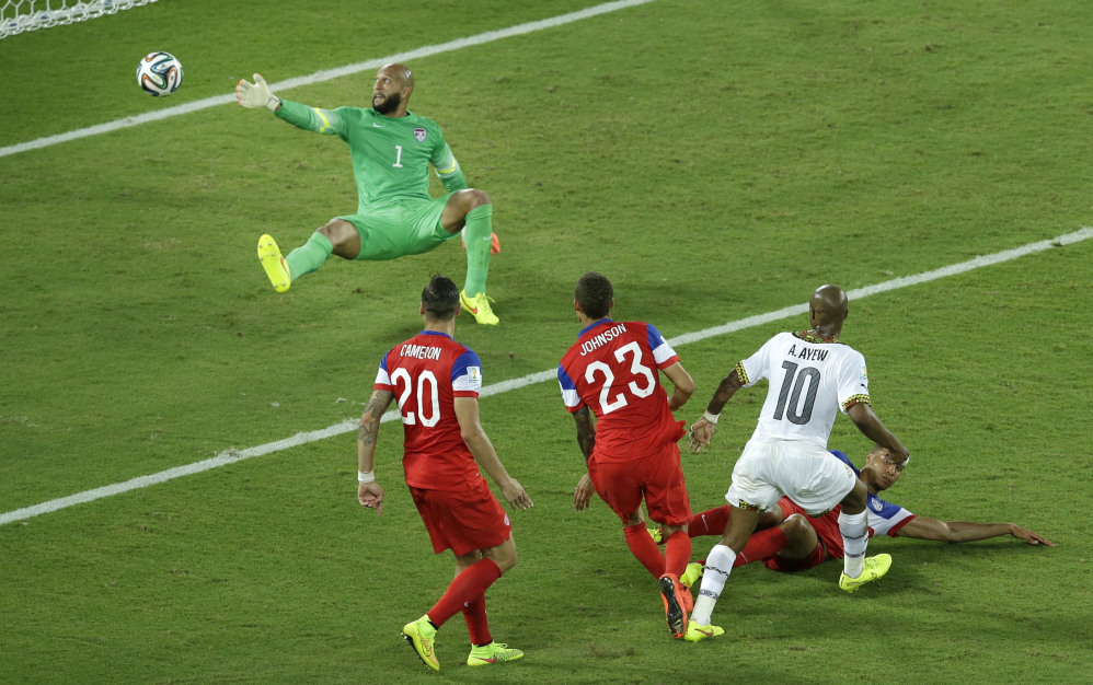 Ghana's Andre Ayew (10), right, scores his side's first goal past United States' goalkeeper Tim Howard.