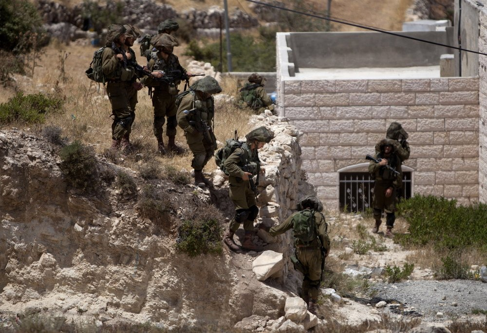 Israeli soldiers conduct a military operation to search for three missing teenagers outside the West Bank city of Hebron on Monday.