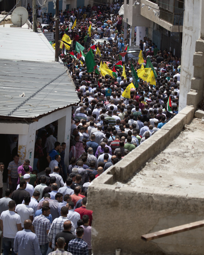Mourners follow the body of slain Palestinian Ahmad Arafat Sabarin, killed by Israeli army fire early Monday during a confrontation between stone throwers and soldiers, at his funeral procession in Jalazoun.