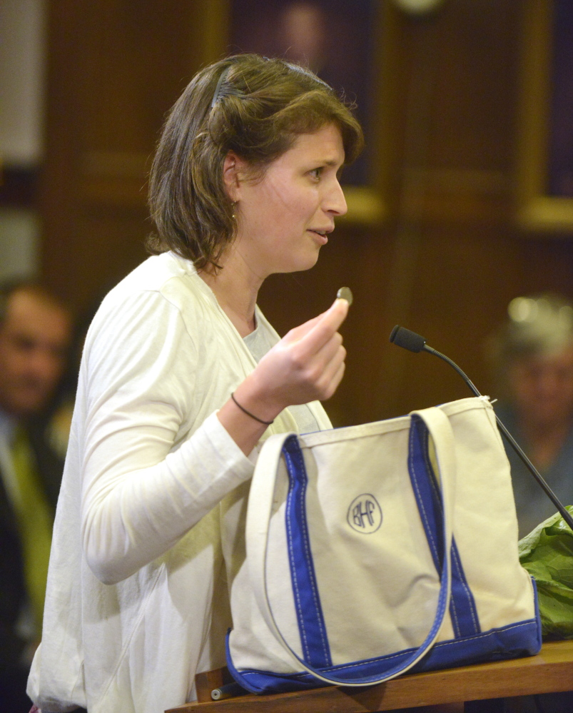 Bonny Frye Hemphill pulls a nickel from her canvas shopping bag Monday night during a discussion with the city council about a fee for disposable shopping bags in Portland.