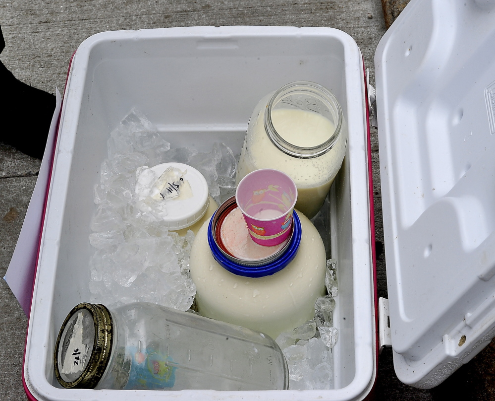 PORTLAND, ME - MAY 13: Raw cows milk and goats milk sit in a cooler to allow people to taste and enjoy it after Farmer Dan Brown joined demonstrators before his trial in Supreme Court. (Photo by Gordon Chibroski/Staff Photographer)