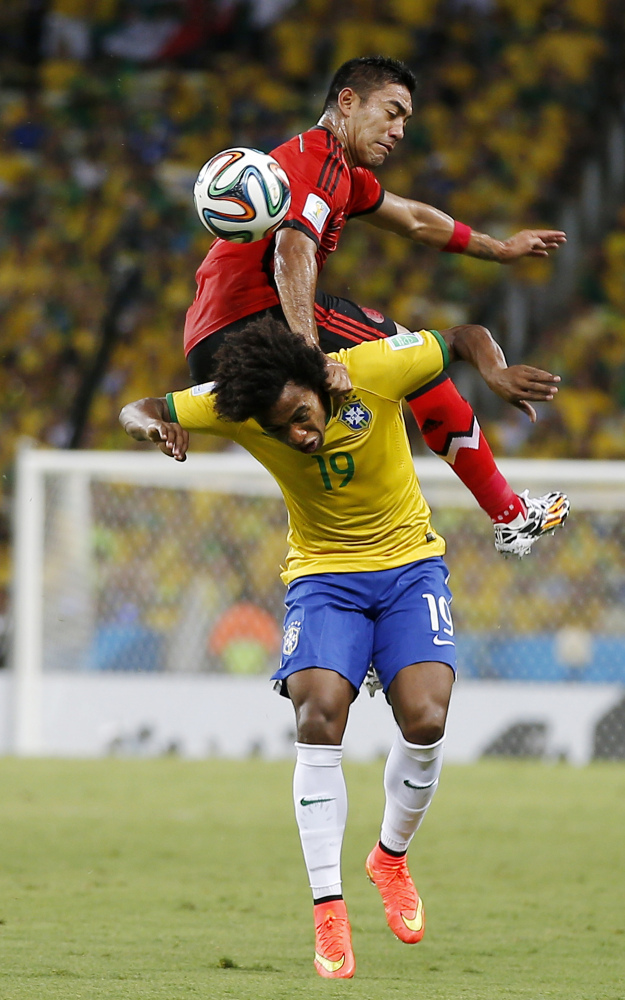 Mexico's Marco Fabian flips over Brazil's Willian while trying to head the ball during the group A World Cup soccer match between Brazil and Mexico.