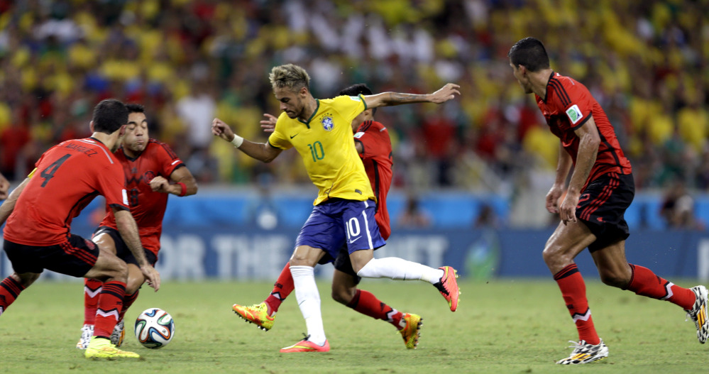 Brazil's Neymar is closed down by the Mexico defense during the group A World Cup soccer match between Brazil and Mexico at the Arena Castelao in Fortaleza, Brazil, Tuesday, June 17, 2014.