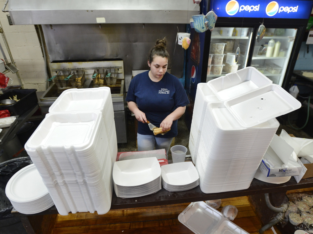 Manager Lindsey Schwarz at Susan's Fish-N-Chips is framed Tuesday by Styrofoam take-out containers that the restaurant will be banned from using starting next April.