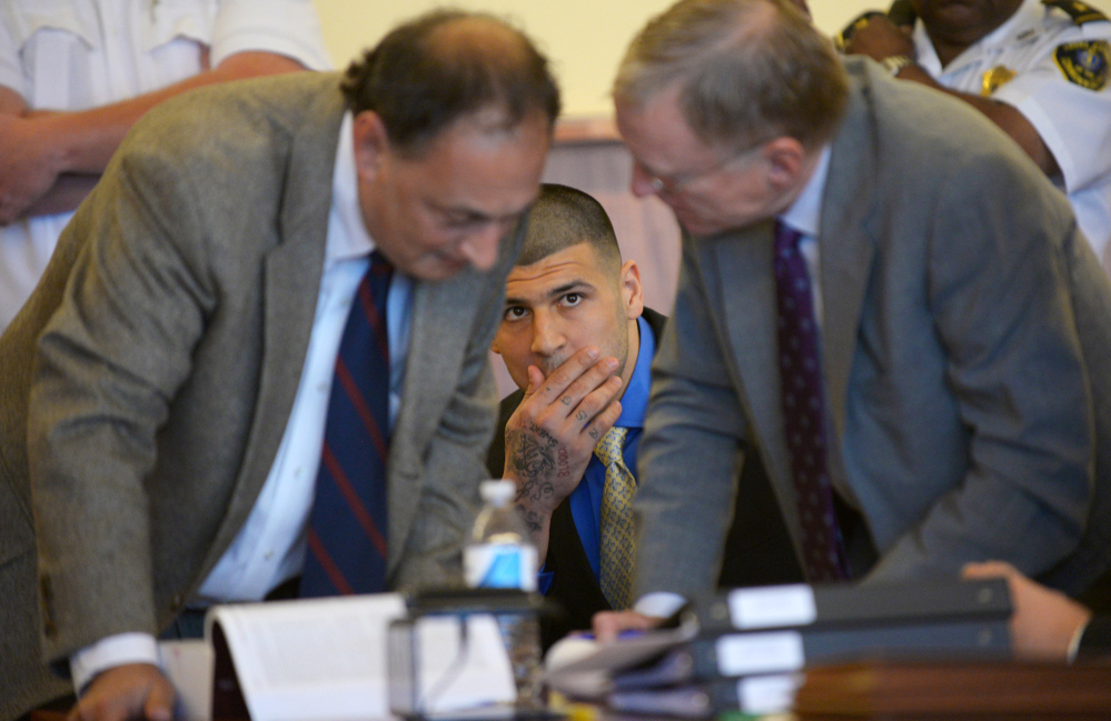 Former New England Patriots NFL football player Aaron Hernandez watches his defense attorneys James Sultan and Charles Rankin during a hearing at the Bristol County Superior Court House on Monday in Fall River, Mass.