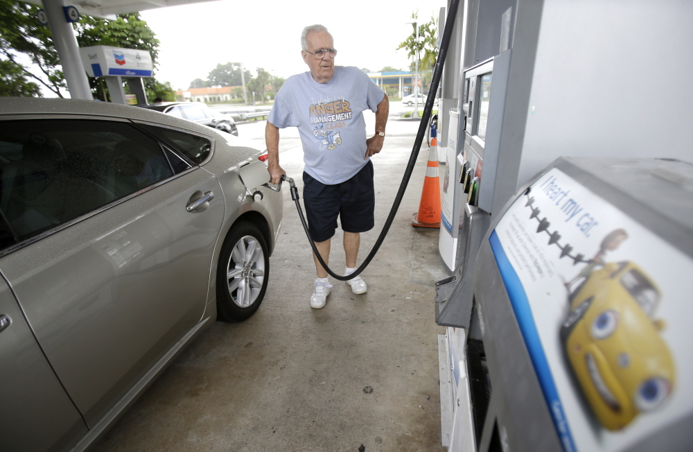 Marty Mascio pumps gasoline into his car at a Chevron gasoline station in Pembroke Pines, Fla. Americans are driving less per capita and cars are more fuel efficient, keeping federal tax revenues fairly flat.