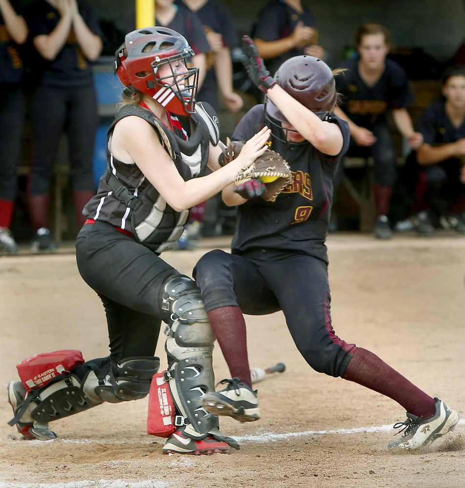 Wells High School catcher Meghan Young holds on to the ball while colliding with Elise Flathers of Cape Elizabeth High School during their Western Class B championship softball game at Saint Joseph's College in Standish on Wednesday.