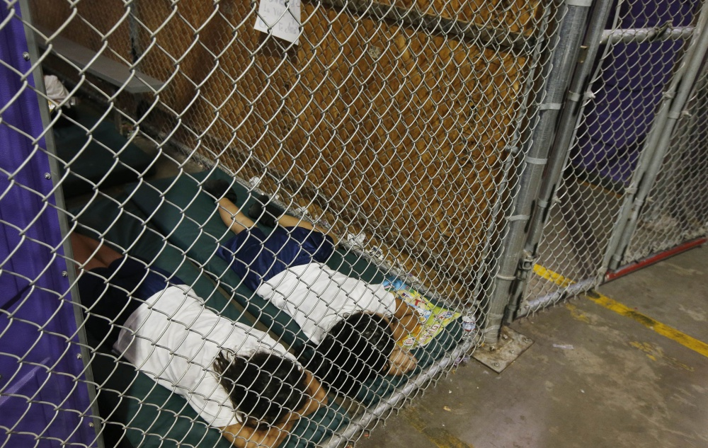 Two female detainees sleep in a holding cell Wednesday at the U.S. Customs and Border Protection placement center in Nogales, Ariz., while awaiting transfer to other shelters.