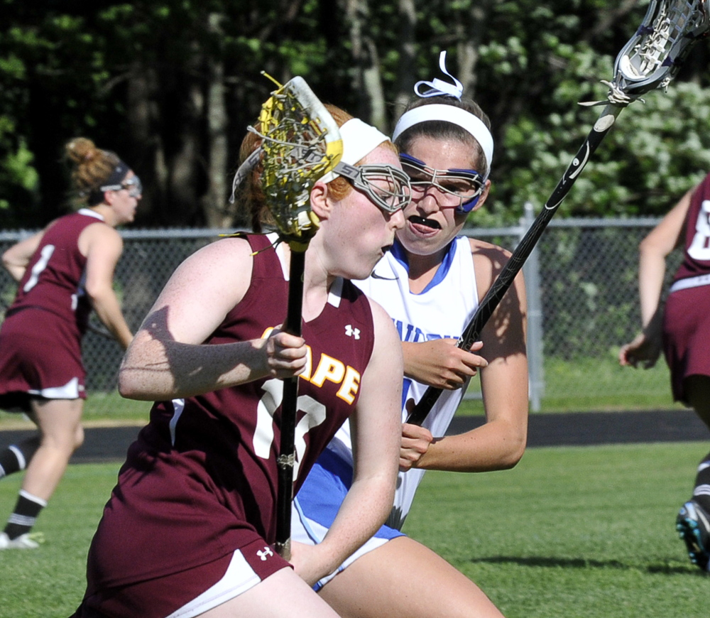Abby McInerney of Cape Elizabeth looks for room past Kennebunk's Jenny Bush in Wednesday's Western Class B final at Cape Elizabeth. The Capers prevailed after losing the previous three regional finals.