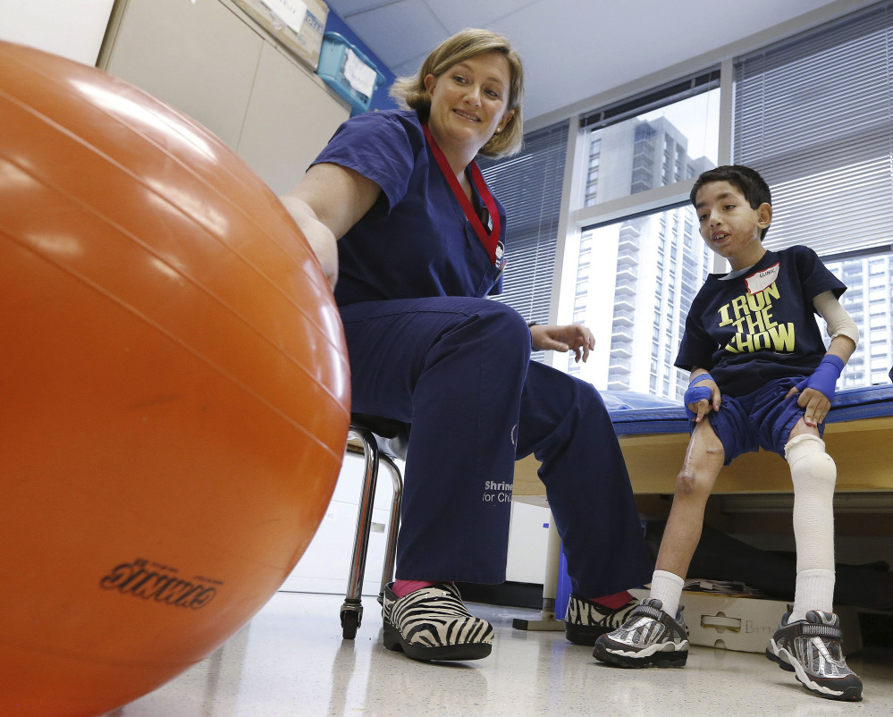 Physical therapist Katherine Hartigan works with Ihor Lakatosh, 11, at Shriners Hospital for Children in Boston last month. Ihor sustained burns in Ukraine in 2011. Neglect had caused his burned skin to contract, fusing his arm to his chest and leaving him unable to walk.