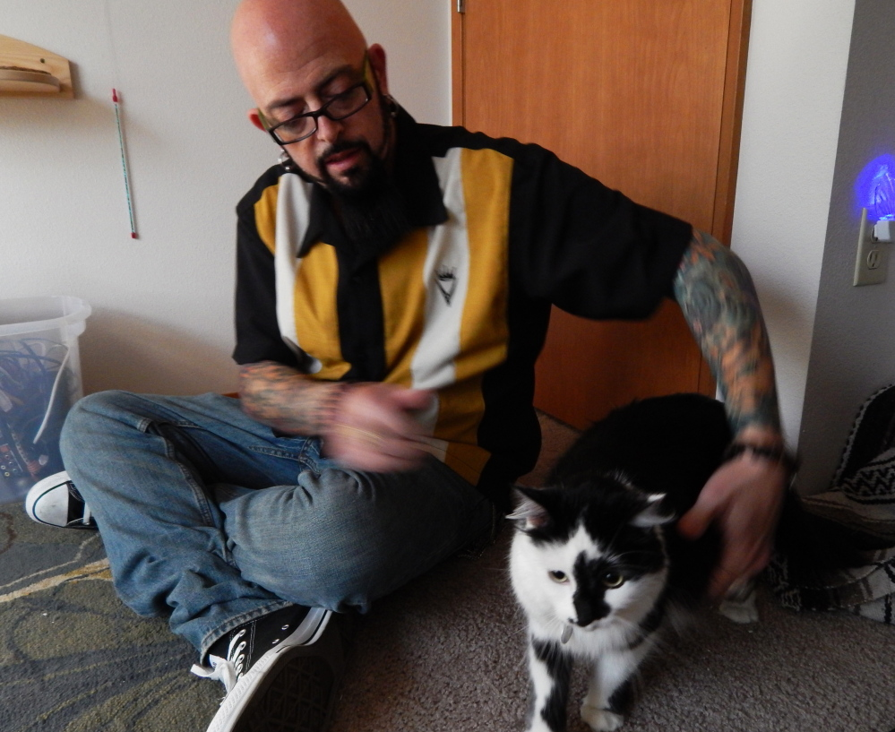 "Jackson Galaxy, host of Animal Planet's ""My Cat From Hell,"" sits in Portland, Ore., with a cat named Lux, whose owners called 911 after Lux boxed them into a bedroom."