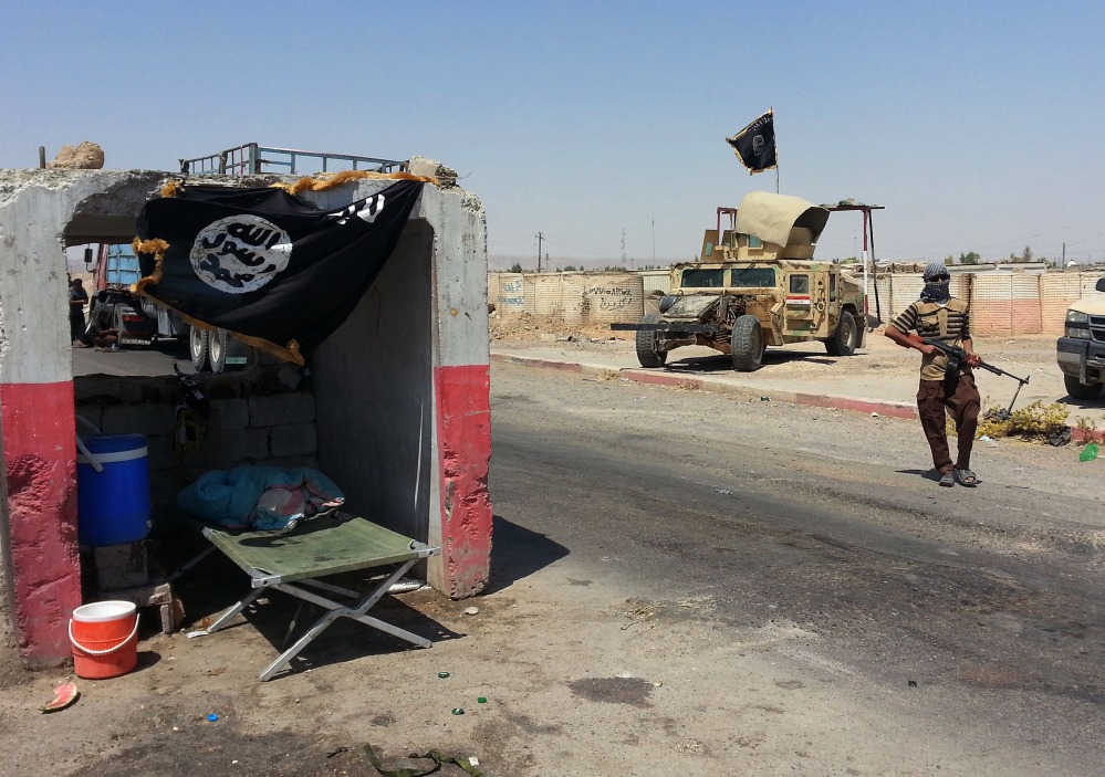 An al-Qaida-inspired militant stands with a captured Iraqi Army Humvee at a checkpoint outside Beiji refinery, some 155 miles north of Baghdad, Iraq, on Thursday.