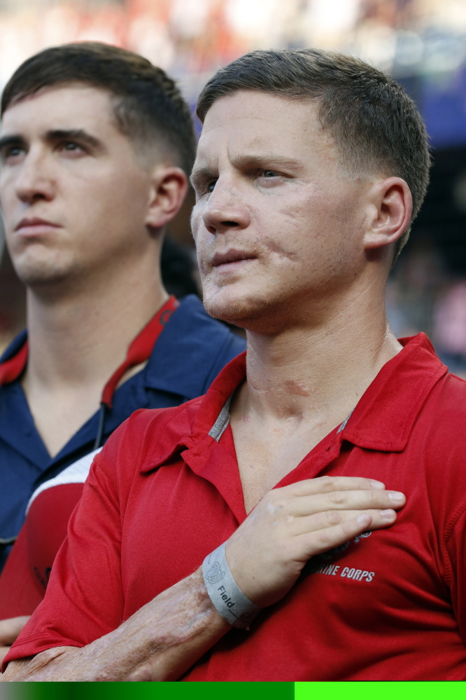 """Retired U.S. Marine Cpl. William """"Kyle"""" Carpenter, right, stands during the National Anthem before a baseball game between the Washington Nationals and the Houston Astros in Washington on Tuesday."""