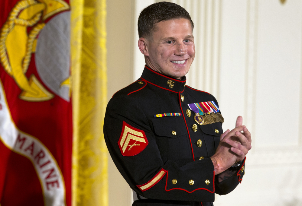 """Retired Marine Cpl. William """"Kyle"""" Carpenter applauds his medical team as they stand to be acknowledged by President Barack Obama during a ceremony presenting Carpenter with the Medal of Honor for conspicuous gallantry, Thursday, June 19, 2014."""