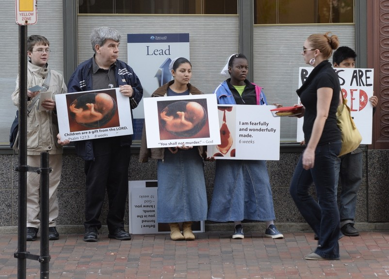 A pedestrian walks past anti-abortion protesters on Congress Street in Portland near the Planned Parenthood clinic in this Oct. 4, 2013, photo.
