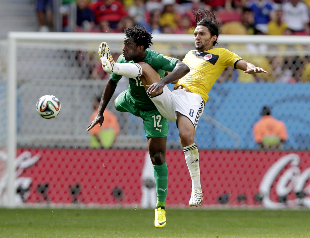 Ivory Coast's Wilfried Bony (12) and Colombia's Abel Aguilar (8) battle for the ball.