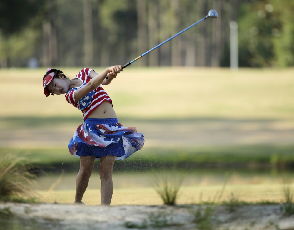 Lucy Li hits from a waste area on the 15th fairway during the first round of the U.S. Women's Open golf tournament in Pinehurst, N.C., Thursday, June 19, 2014.