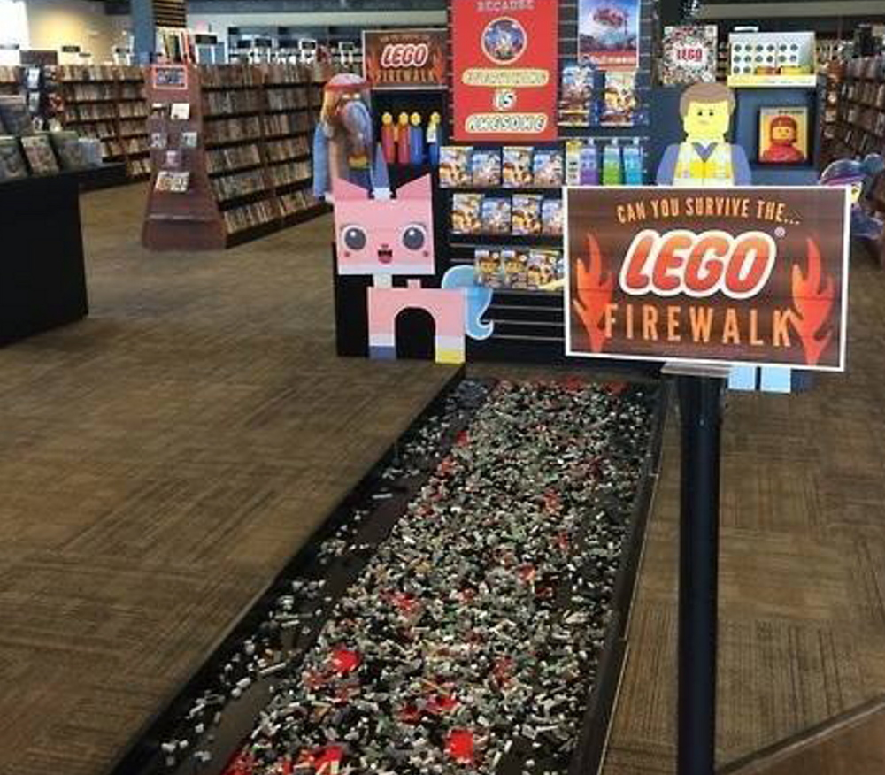 "Customers at Bull Moose in South Portland earned a discount on ""The Lego Movie"" DVD if they could scoot barefoot across the ""fire walk"" of Lego pieces Tuesday."
