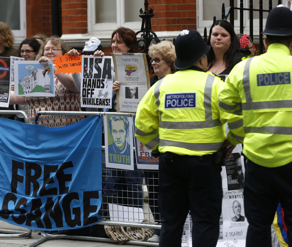 Supporters of WikiLeaks founder Julian Assange hold a vigil outside the Ecuadorian Embassy in London to mark his two years in refuge at the embassy Thursday.